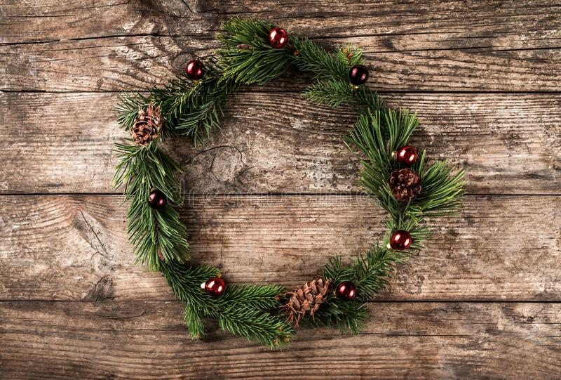 Christmas wreath of Fir branches, cones, red decoration on wooden background with snowflakes. Xmas and Happy New Year royalty free stock image