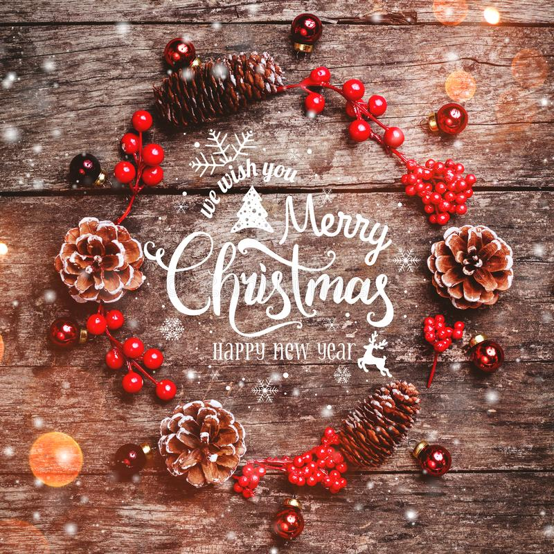 Christmas wreath of Fir branches, cones, red decorations on dark wooden background. Xmas and Happy New Year composition stock images