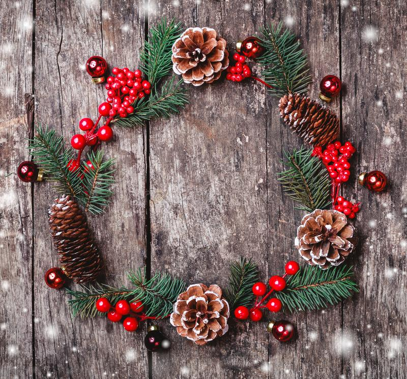 Christmas wreath of Fir branches, cones, red decorations on dark wooden background. Xmas and Happy New Year composition. Flat lay, top view stock photos