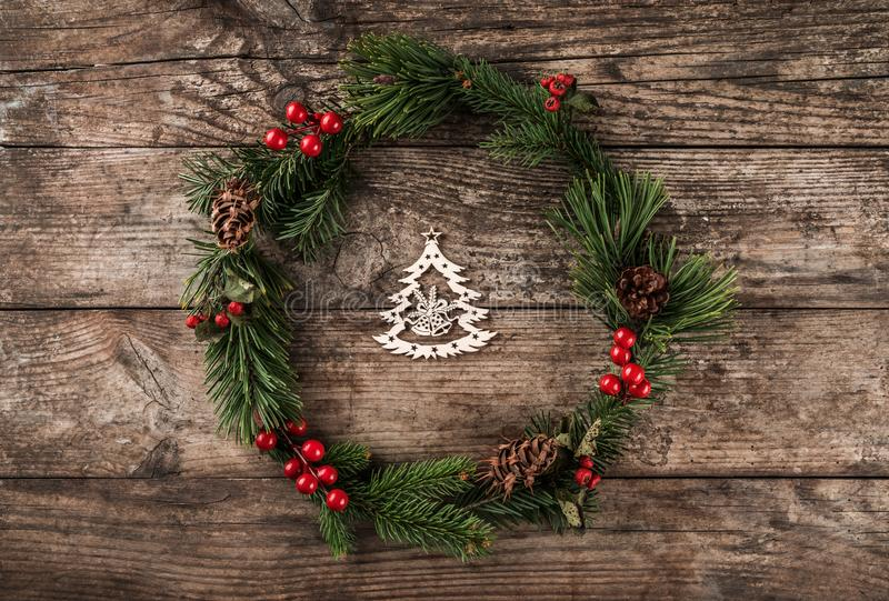 Christmas wreath of Fir branches, pine cones, berries and figurine of wood Christmas tree on rustic background. Xmas and Happy New Year composition. Flat lay stock image