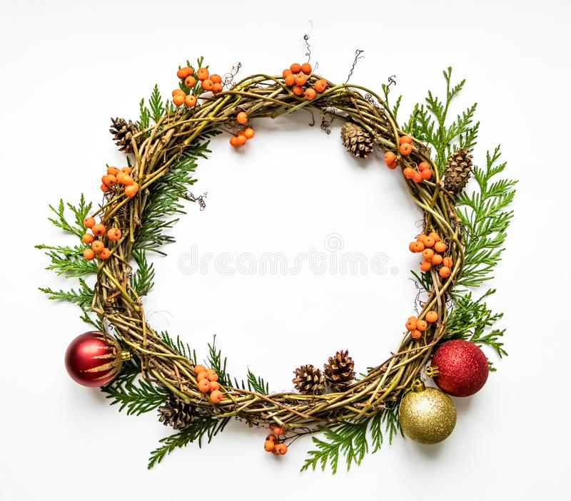 Christmas wreath of vines with decorative ornaments, thuja branches, rowanberries and cones. Flat lay, top view stock photos