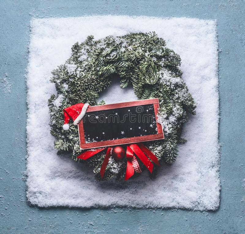 Christmas wreath with green fir branches and red framed sign and Santa hat in snow on blue background, top view with chalkboard stock photos