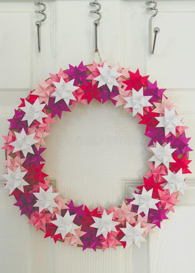 Christmas wreath hanged on white door in room in matt dull colours royalty free stock images