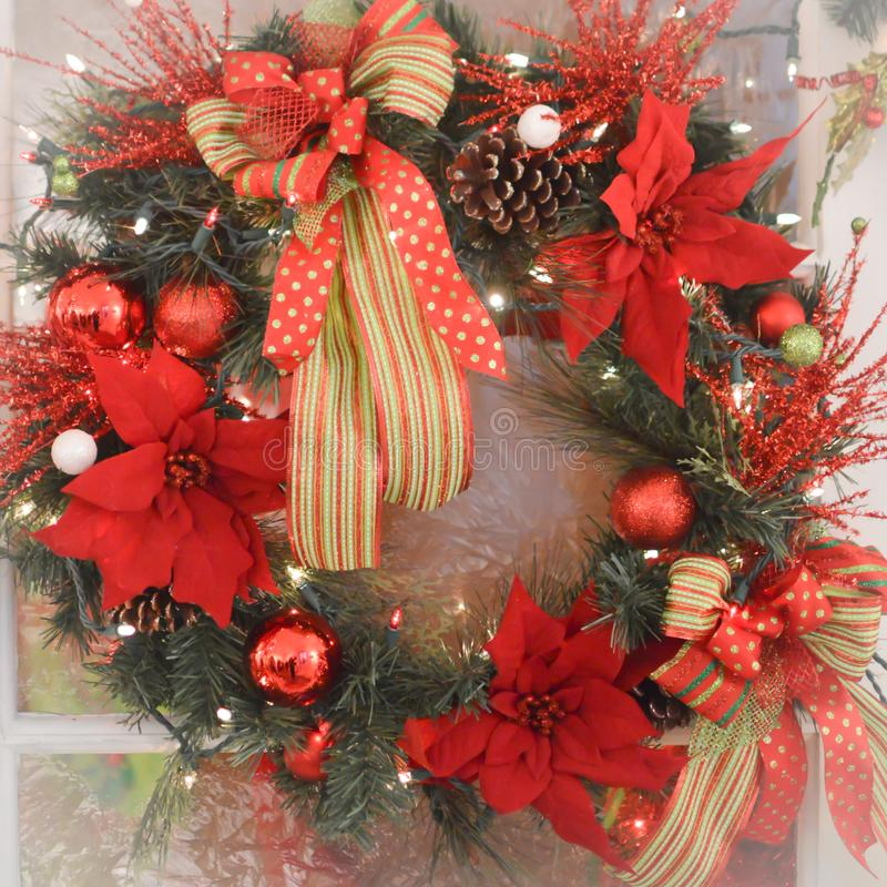 Christmas Wreath with Poinsettia Flowers. A Christmas holiday wreath for the door with red and green ornament balls and pine cones, poinsettia flowers and red stock image