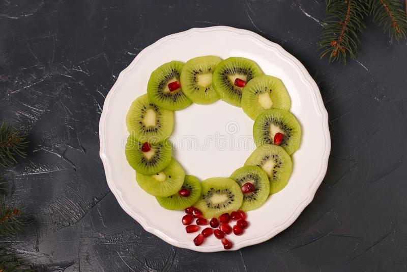 Christmas wreath, snack of kiwi and pomegranate, creative food art idea stock photo