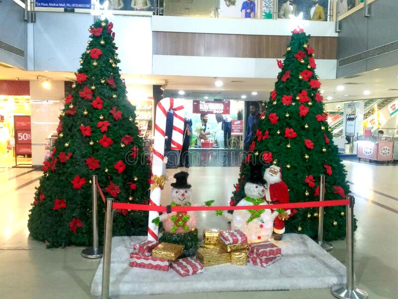Christmas Decoration in Shopping Center. Christmas or Xmas Decoration in a Shopping Mall. Xmas tree decorated with red flowers alongwith Snow mans and Santa stock image