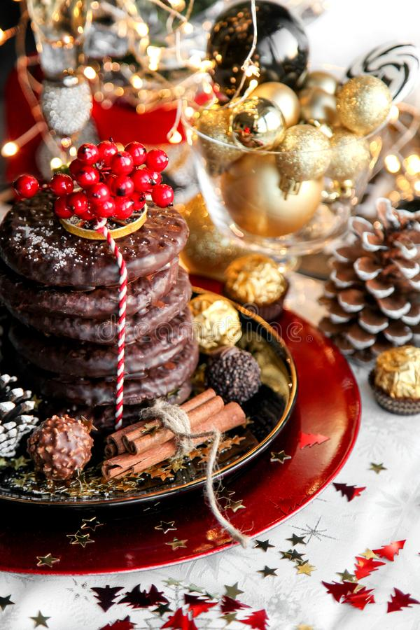 Christmas, xmas ginger bread with rowan, mountain ash and sweets, cookies on red plate, golden balls and confetti with cinnamon,. Chrismas cone royalty free stock photography