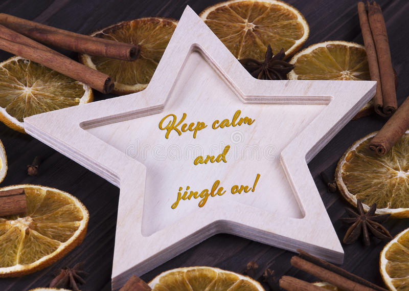 Christmas Xmas New Year Holiday card with wooden star cinnamone star anice dried oranges and text Keep calm and jingle on royalty free stock photos
