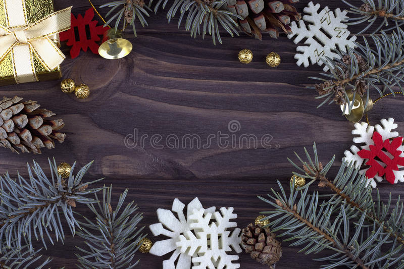 Christmas Xmas New Year holiday decoration with golden bells balls red white snowflakes natural fir branches and cones on dark woo royalty free stock photo