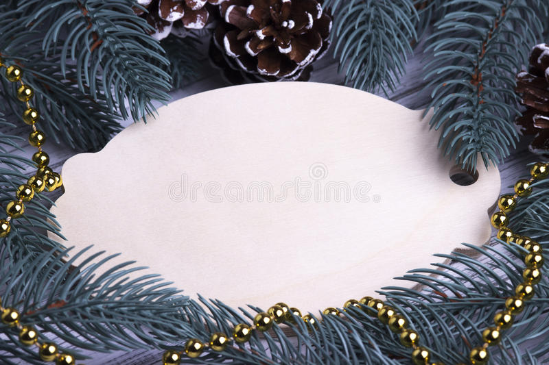 Christmas Xmas New Year Holiday greeting card concept with empty wooden tablet fir branches cones gold necklace space for text dec royalty free stock photos
