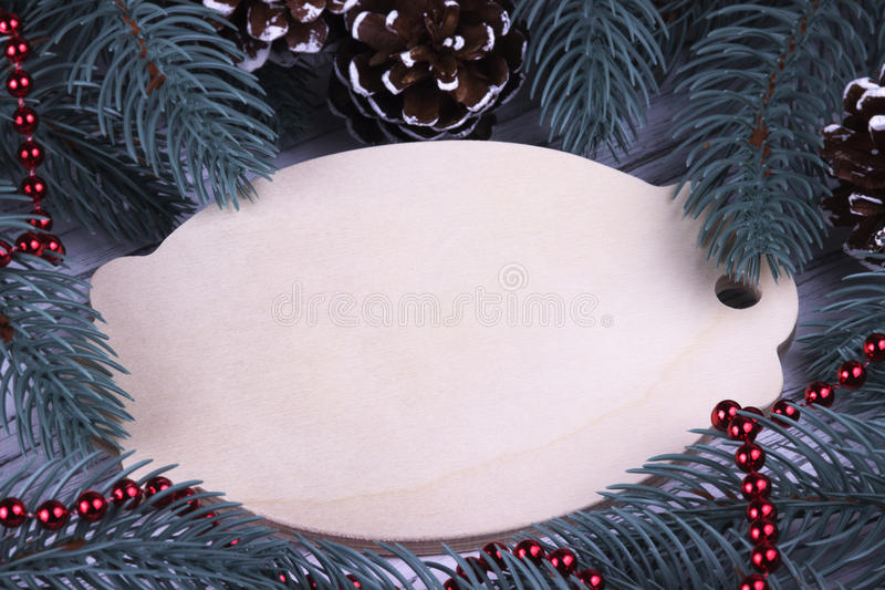 Christmas Xmas New Year Holiday greeting card concept with empty wooden tablet fir branches cones red necklace space for text deco stock photography