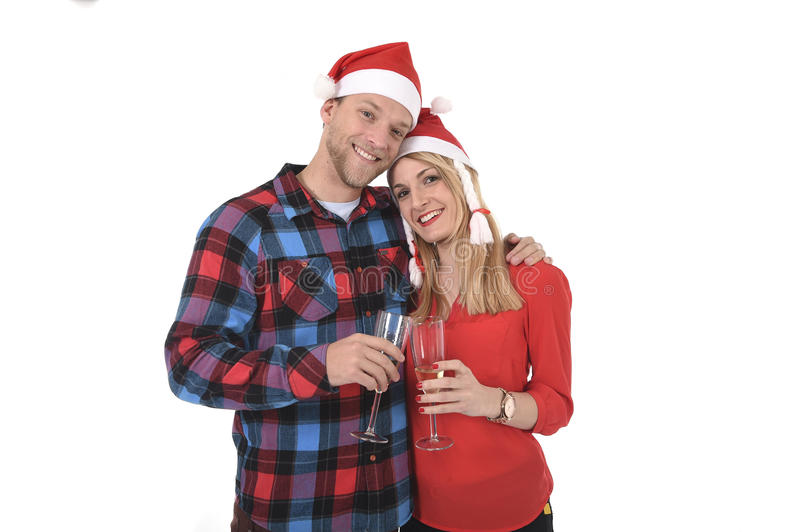 Christmas young beautiful couple in Santa hats in love smiling happy together Champagne glasses toast. Wearing trendy clothes isolated on white background stock photo