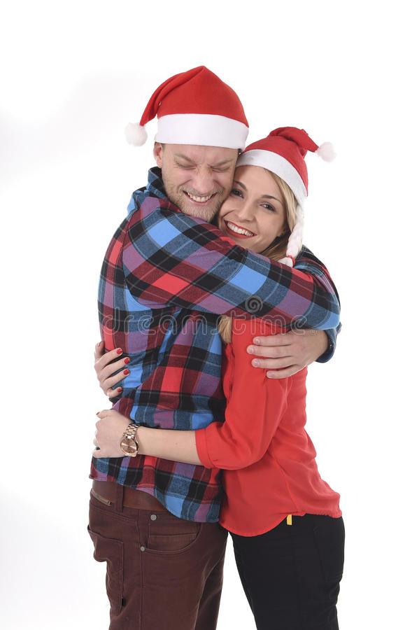 Christmas young beautiful couple in Santa hats in love smiling happy together hugging each other sweet stock photos