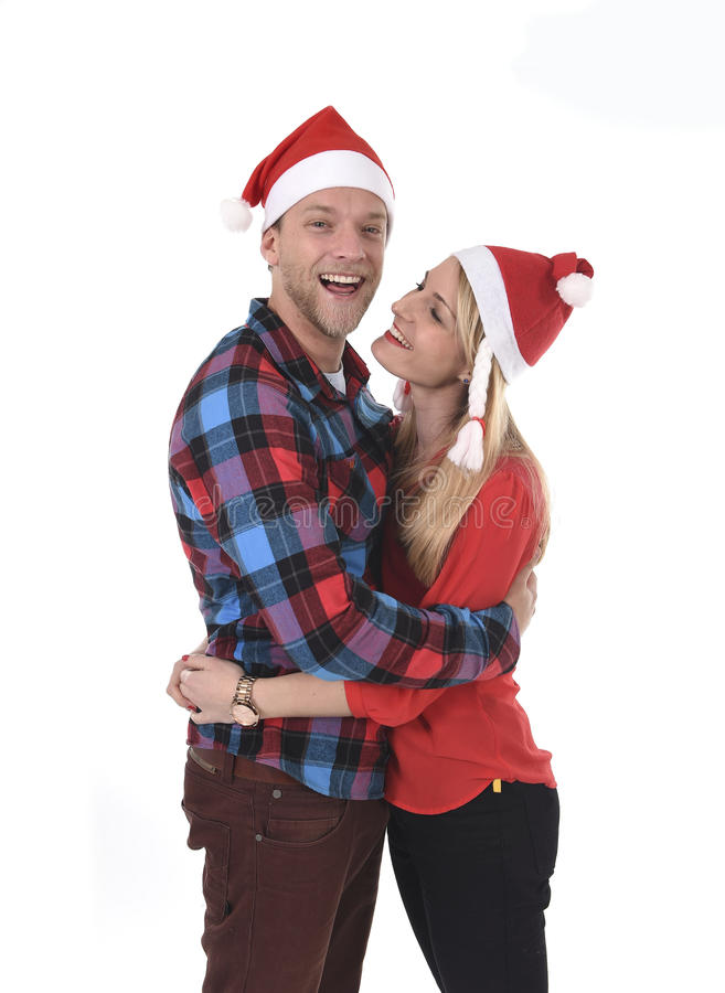 Christmas young beautiful couple in Santa hats in love smiling happy together hugging each other sweet. Wearing trendy clothes isolated on white background stock photography