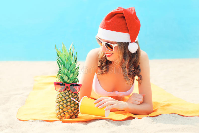 Christmas young smiling woman in red santa hat with pineapple cup fresh fruit juice lying on beach over blue sea stock photo
