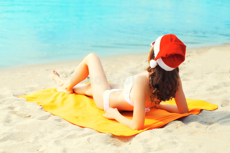 Christmas young woman in red santa hat relaxing lying on sand beach over sea stock photo