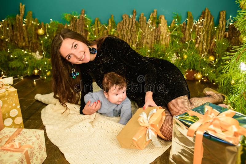 Christmas with your beloved mom. Merry Christmas and happy holidays Cute son gives a present to his beloved mother. New interior royalty free stock images