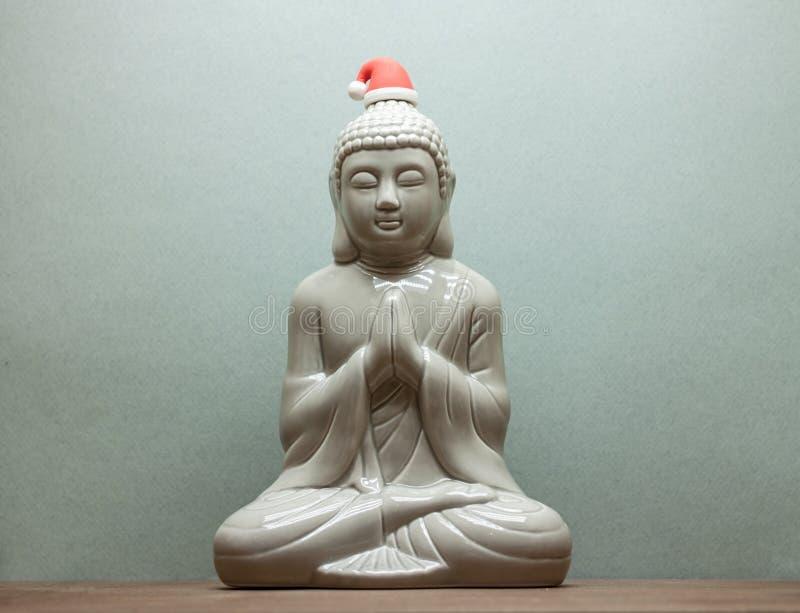 Christmass Buddha i den röda santa hatten på blå bakgrund royaltyfri fotografi