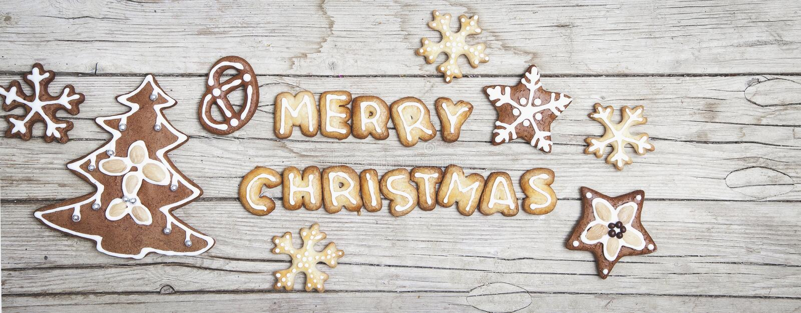 Christmassy grey wood background with gingerbread and Merry Christma`s letter stock photography
