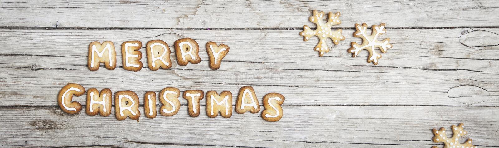 Christmassy grey wood background with gingerbread and Merry Christma`s letter royalty free stock image