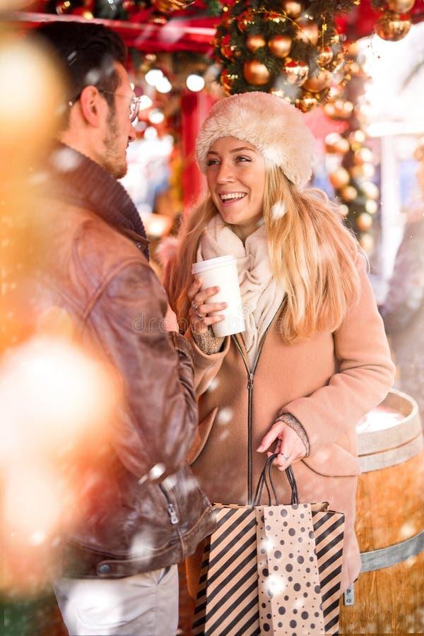 christmastime Ett par som shoppar för jul och dricker coffe royaltyfri foto