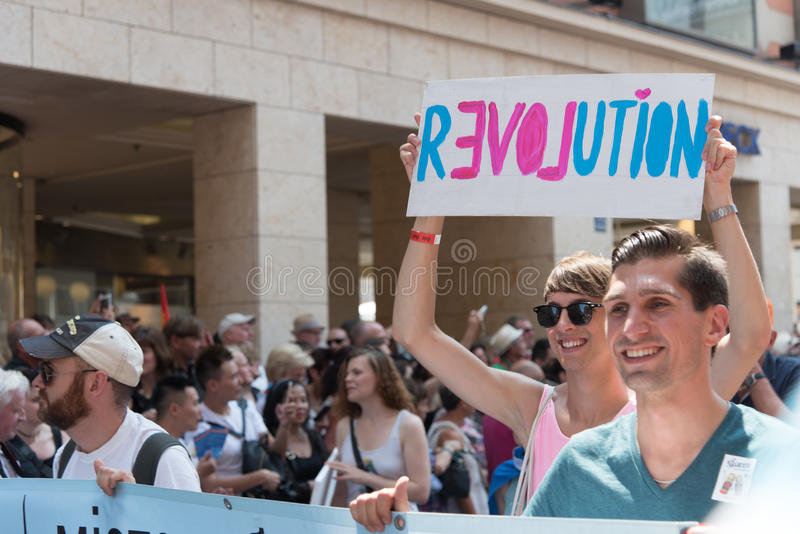 Christopher Street Day Munich 2015 - Revolution. MUNICH, GERMANY - 11 JULY 2015: Christopher Street Day - A man in the parade holding a plate with the word stock photos