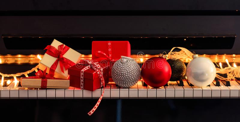 Chritmas balls and gift boxes on piano keyboard, front view royalty free stock image