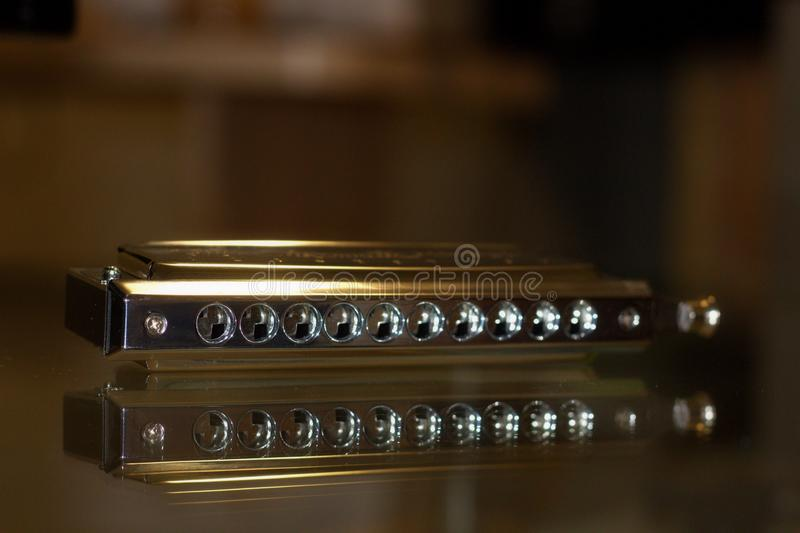 Chromatic harmonica on a glass table. Chromatic harmonica in the box, wind-tongued tongue musical instrument, lips and tongue used for jazz, blues, country, folk royalty free stock photos