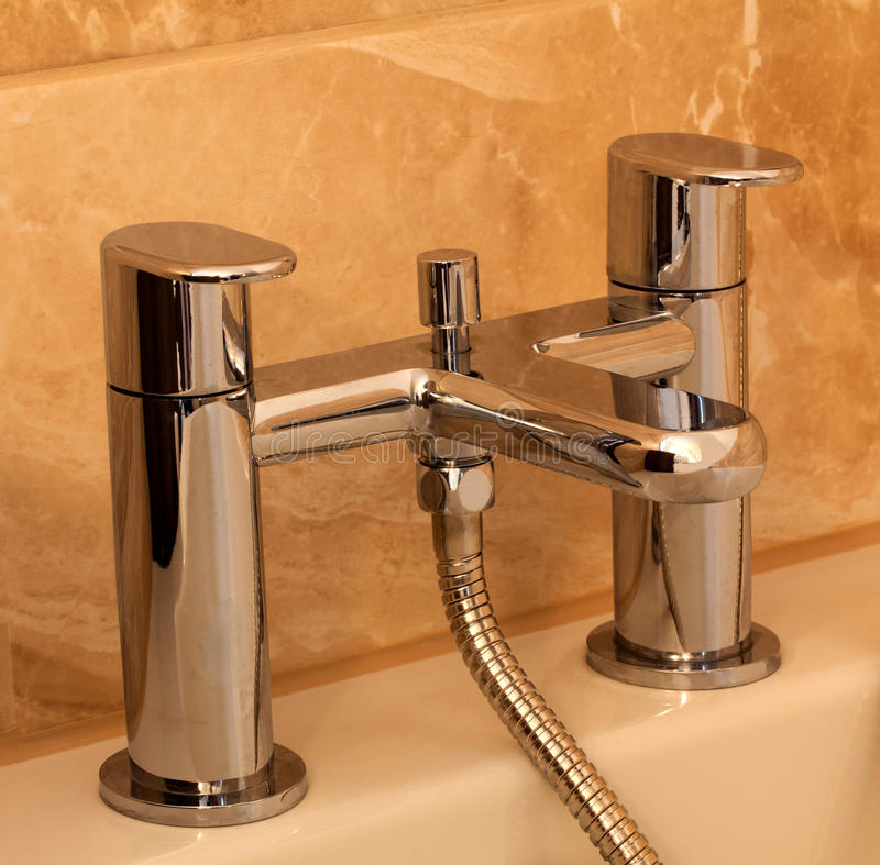 Chrome bathtub faucet. A modern mixer chrome bath taps with marble effect tiles in the background stock photo