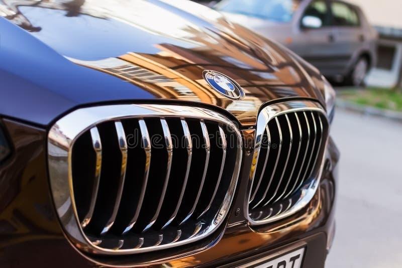 Chrome BMW商标标志特写镜头 黑蓝色BMW前面敞篷和汽车格栅在室外停车处的在一好日子 库存照片