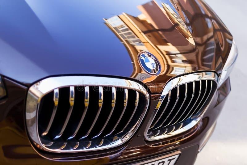 Хромированная вывеска с логотипом BMW крупным планом. Автомобильная решетка и передний капот черно-синего BMW на открытой парковке в солнечный день. Городские отражения. На капоте автомобиля стоковая фотография