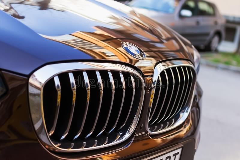 Chrome BMW logo sign close-up. Front hood and car grill of black blue BMW on an outdoor parking on a sunny day. Varna, Bulgaria, February 20, 2019. Chrome BMW stock photos