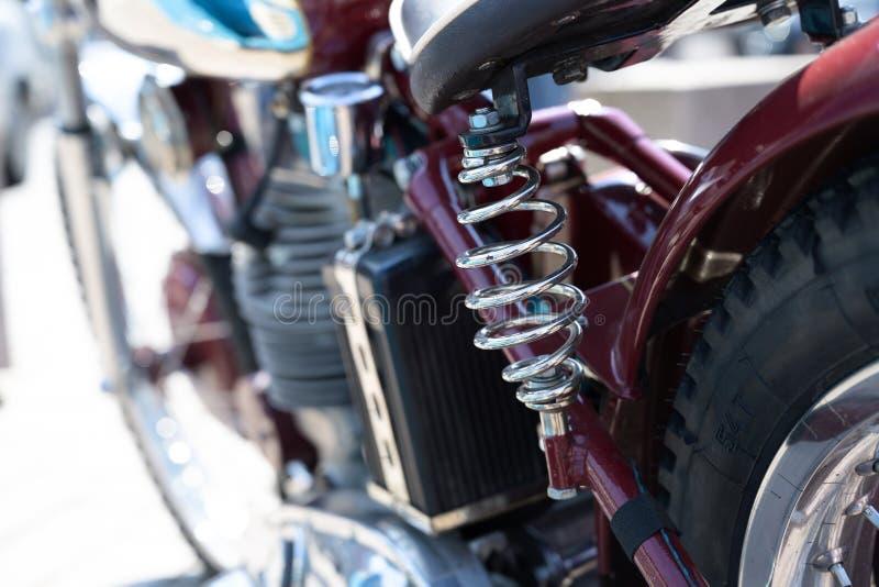 Chrome chapeou a mola espiral sob a sela de uma motocicleta cl?ssica vermelha, foco selecionado do amortecedor fotos de stock royalty free