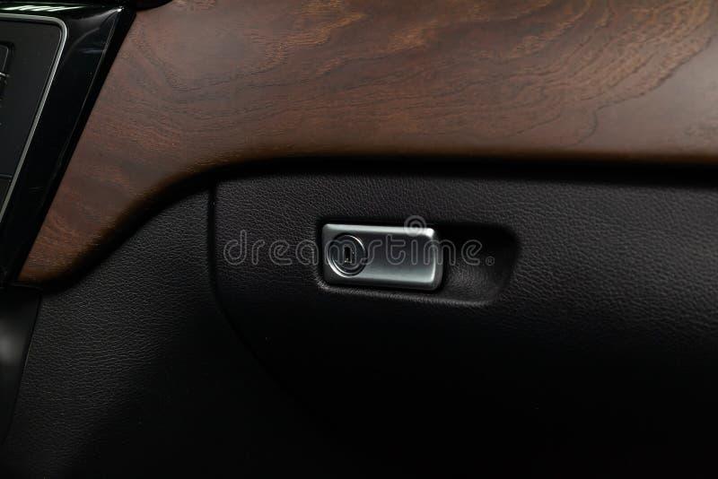 Chrome chapeou o fechamento e o punho para abrir no compartimento de luva do carro ao lado da guarnição de madeira fotos de stock