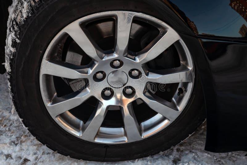 Chrome chapeou a roda do alumínio de molde no carro com um pneu de borracha preto, os cinco furos para os parafusos de montagem e fotografia de stock royalty free