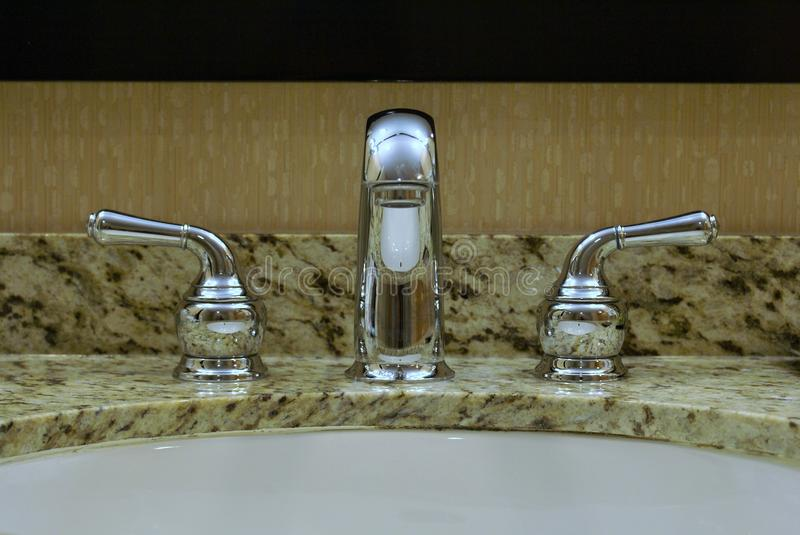 Chrome fawcett and taps. Chrome washbasin taps and a separate Fawcett on a granite base in a bathroom. The taps have a highly polished mirror appearance stock photo