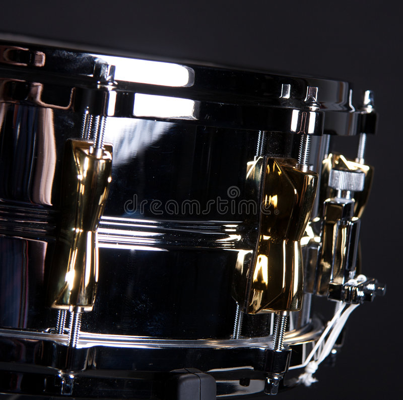 Chrome and Gold Snare Drum. A chrome and gold snare drum isolated on a black background in the horizontal format with copy space stock image