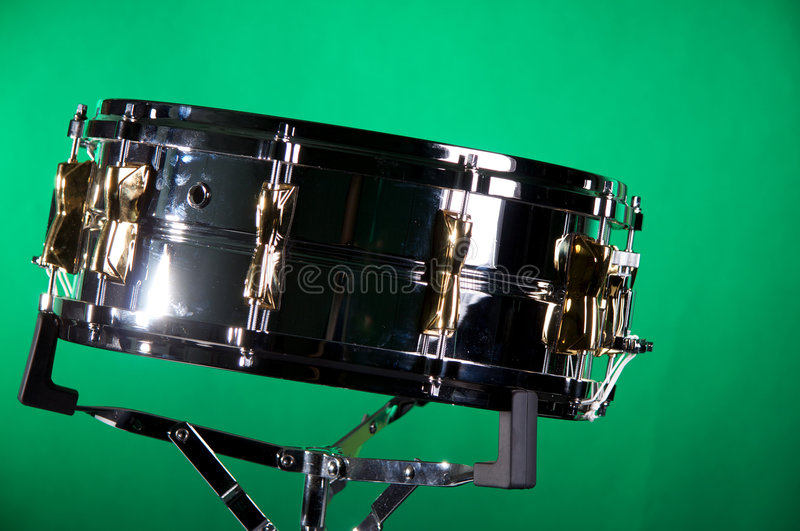 Chrome and Gold Snare Drum. A chrome and gold snare drum isolated on a green background in the horizontal format with copy space stock photography