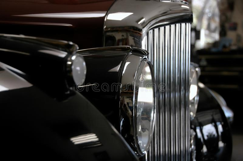 Chrome nostalgia. Headlamp and grille detail of classic antique car, black, burgundy and chrome royalty free stock photo