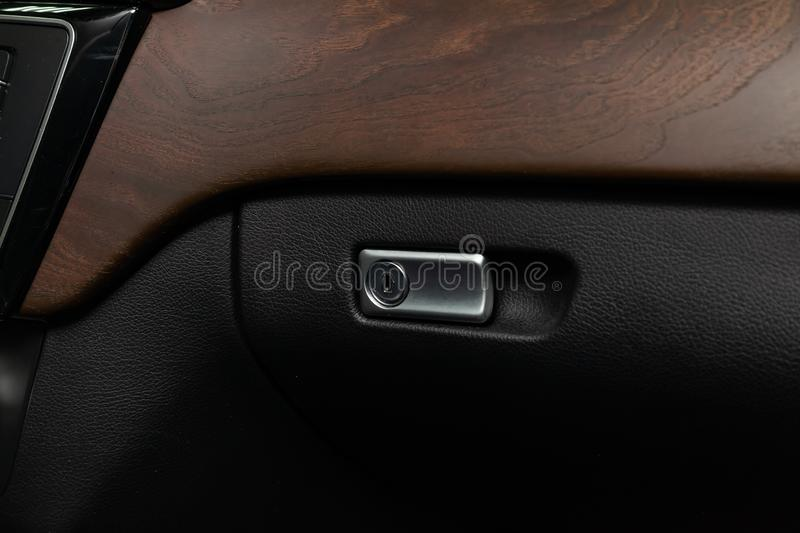 Chrome-plated lock and handle for opening on the glove compartment of the car next to the wooden trim. Of the vehicle stock photos