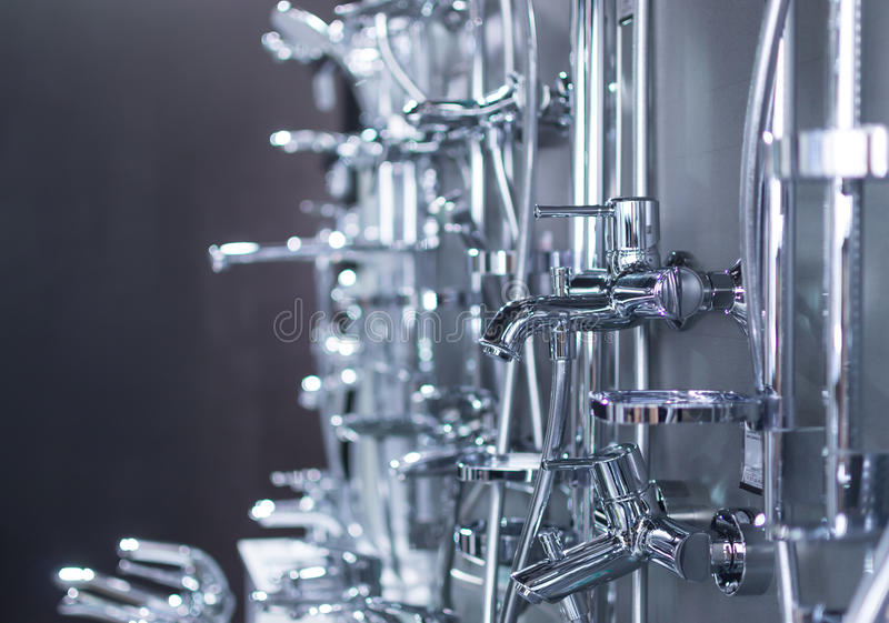 Chrome Shower Heads and Taps. Many chrome shower heads and kitchen bathroom taps on display stock photo