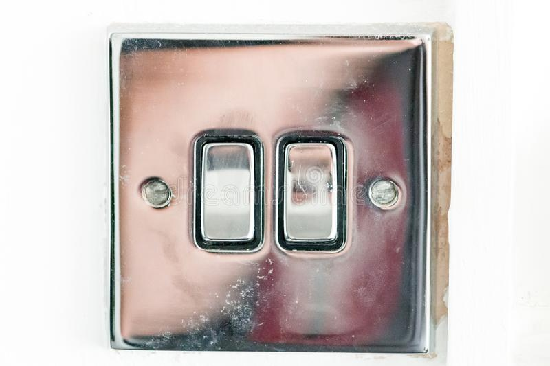 Chrome Switch. A polished chrome light switch on a white wall royalty free stock photography