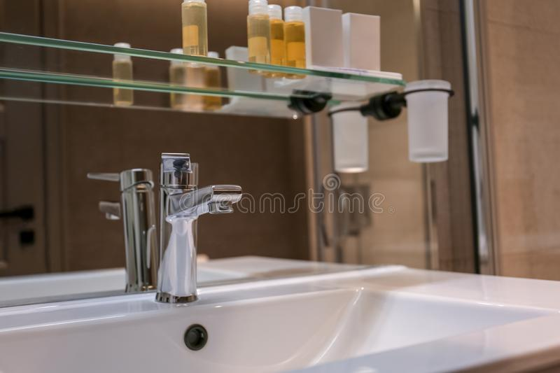 Chrome tap and white sink. In bathroom royalty free stock photo