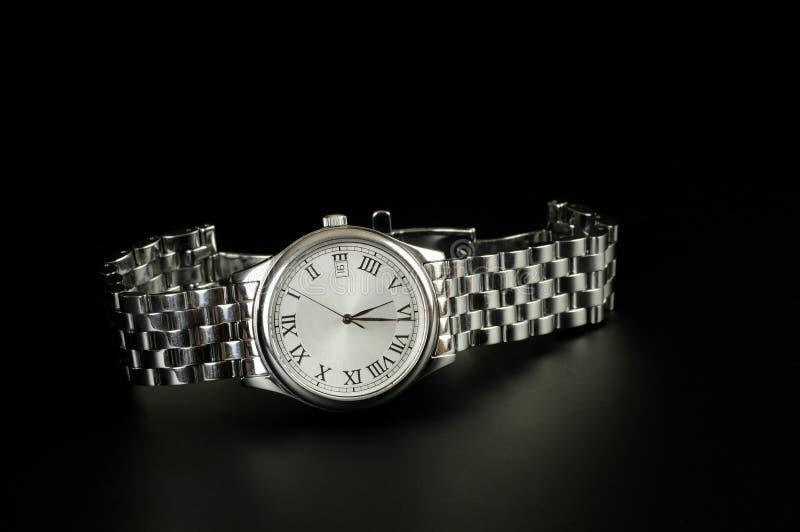 Chrome watch on black. Background stock photos
