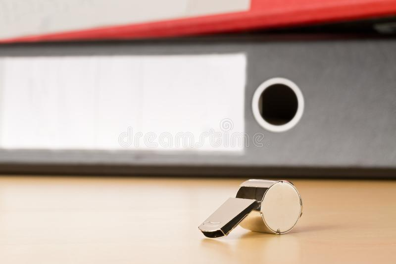 Chrome whistle in front of folders with confidential top secret information on wooden office desk - whistleblower concept stock photos