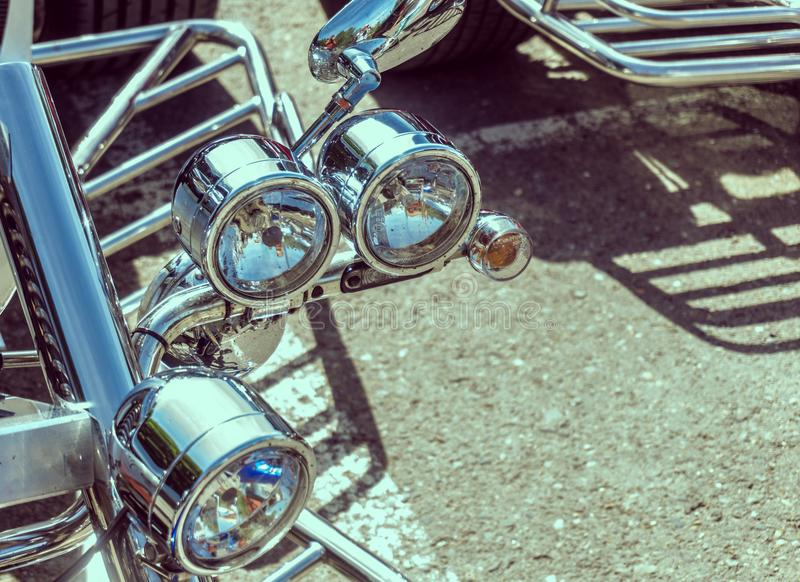 Chromed headlights on the front fork of a trike royalty free stock photo