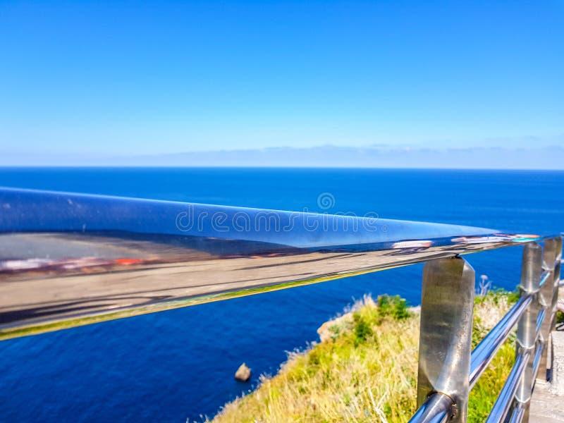 Chromed r?cke med bakgrund f?r bl? himmel och havs arkivfoton