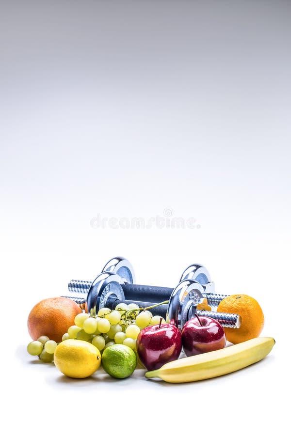 Chromuje dumbbells otaczających z zdrowych owoc pomiarową taśmą na białym tle z cieniami fotografia stock