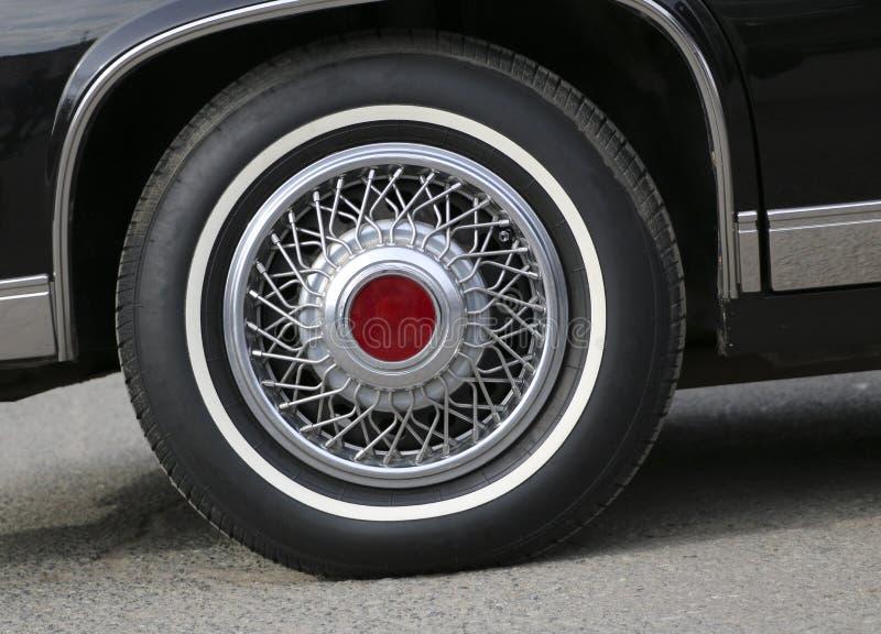 Chromuje koło z srebrzystymi szprychami i nową gumą na czarnym błyszczącym Cadillac obraz royalty free