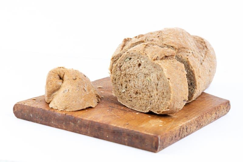 Chrono- pain coupé en tranches avec des céréales sur la planche à découper photo stock